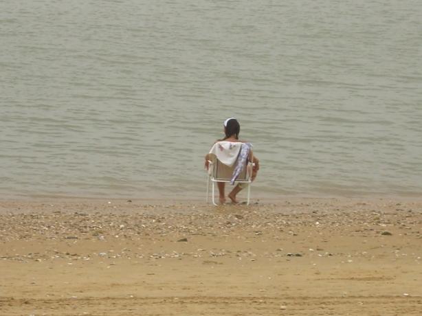Una señora en la orilla de la Playa de La Calzada de Sanlúcar